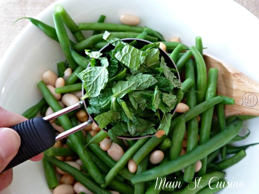 adding fresh mint to the three bean salad